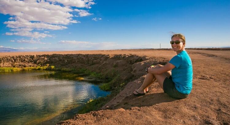 Uma mulher sentada em frente à laguna cejar em San Pedro de Atacama