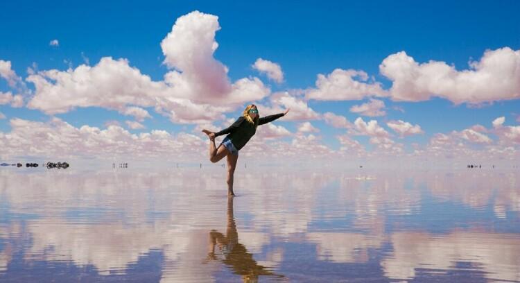 Mulher fazendo uma pose no Salar de Uyuni com efeito de espelho.