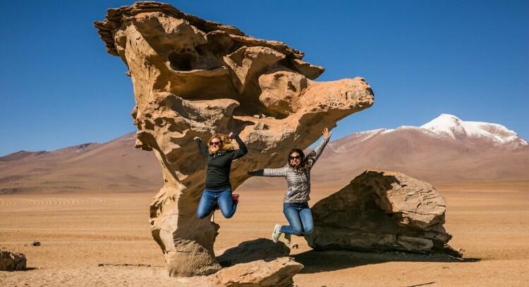 Personas saltando frente al árbol de piedra.
